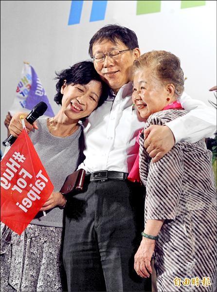 柯文哲昨在抵達遊行終點市政府時,將母親何瑞英(右)與妻子陳佩琪(左)緊緊抱在一起。(記者王敏為攝)