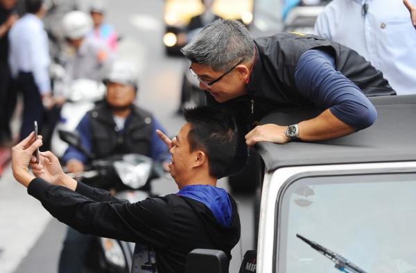 選戰進入最後倒數,台北市長候選人連勝文(右)今日以車隊掃街,爭取選票,一挺連民眾上前與連自拍合影。(記者張嘉明攝)