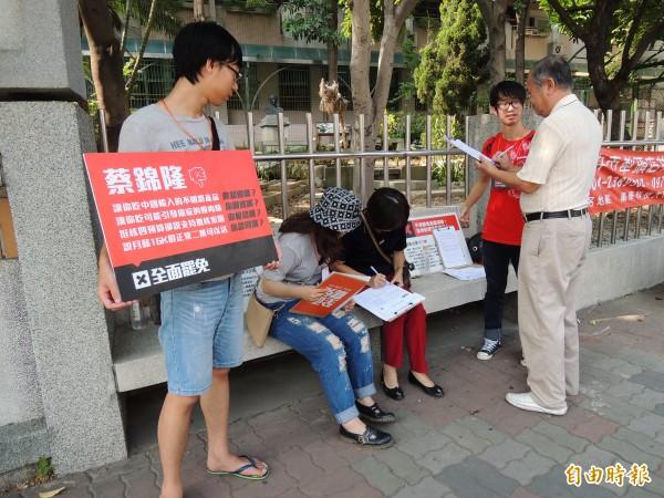 「全面罷免」團體今天上午在南屯區文山國小投開票所外,向投票民眾徵求罷免立委蔡錦隆的連署書。(記者許國楨攝)