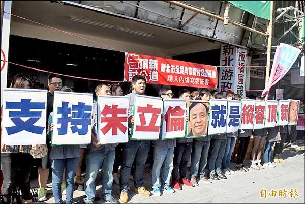民進黨新北市長候選人游錫堃競選後援會前,青年手持抗議標語,高喊「支持朱立倫,就是縱容頂新」。(記者陳韋宗攝)