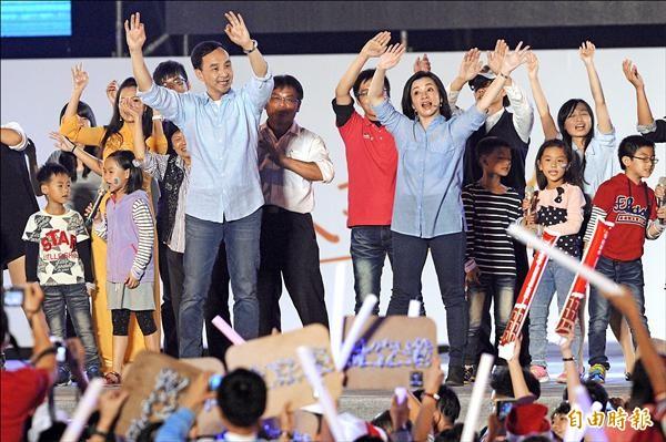 新北市長候選人朱立倫(左)昨在板橋第一運動場舉行選前團結之夜,與妻子高婉倩(右)在台上合唱歌曲。(記者陳志曲攝)