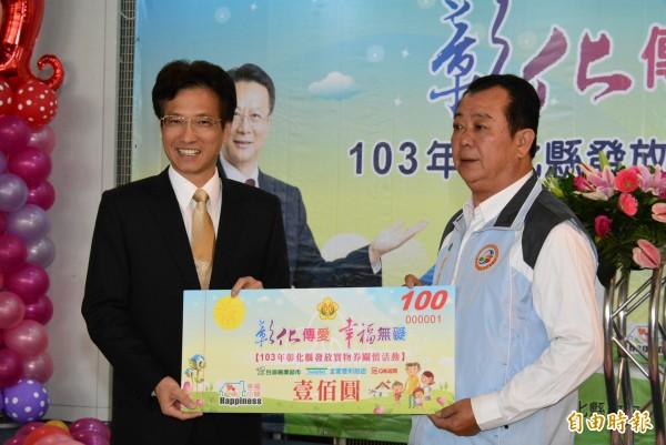 彰化縣副縣長林田富(左)今天發放實物券樣本。(記者吳為恭攝)