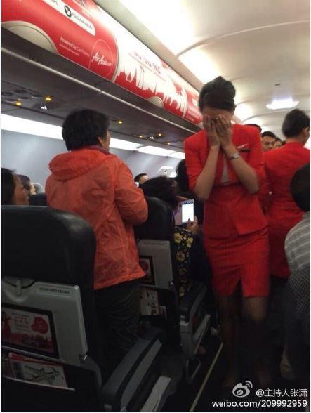 空姐受到男子的辱罵,無法有效控制衝突場面,掩面哭泣。(圖擷取自主持人張瀟微博)