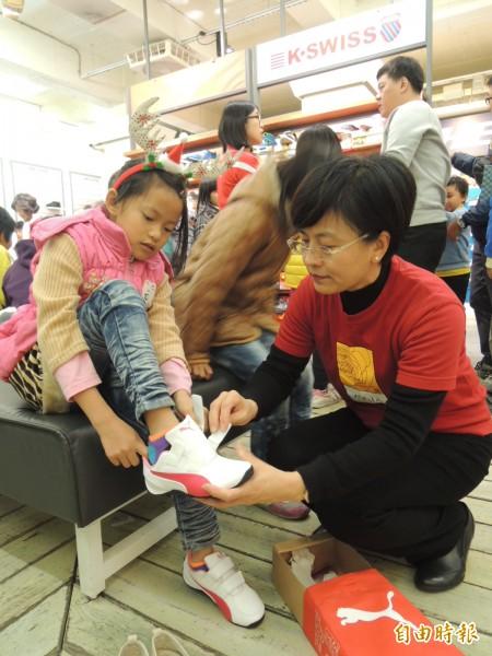 崇她媽媽戴麗美幫小朋友試穿新鞋。(記者余雪蘭攝)