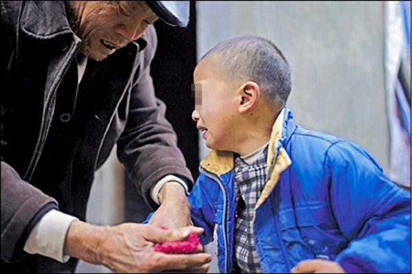 化名坤坤的四川西充縣8歲愛滋病童,正由爺爺為他洗手,因為手上凍裂,沾水特別疼痛。(取自網路)