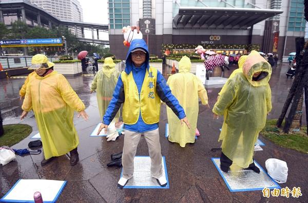 昨下午法輪功成員照常在台北一○一前練功。(記者方賓照攝)