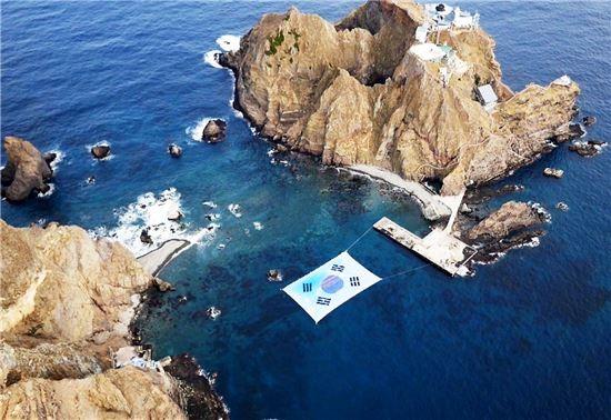 日本韓國對於主權有爭議的島嶼「獨島」(日本稱竹島)出現了面超大韓國國旗,是由韓國大學教授徐坰得所做的。(圖擷取自http://www.asiae.co.kr/)