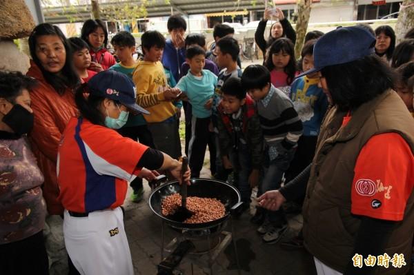 後埤社區長者製作花生糖,公館國小學生圍觀學習。(記者王揚宇攝)