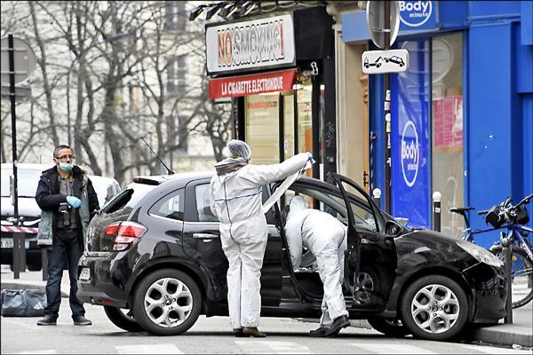 法國「查理週刊」七日遭槍手攻擊造成至少十二人死亡,成為法國近四十年來最嚴重的攻擊事件,鑑識人員進駐現場,針對槍手搭乘的車輛採集證據。(法新社)