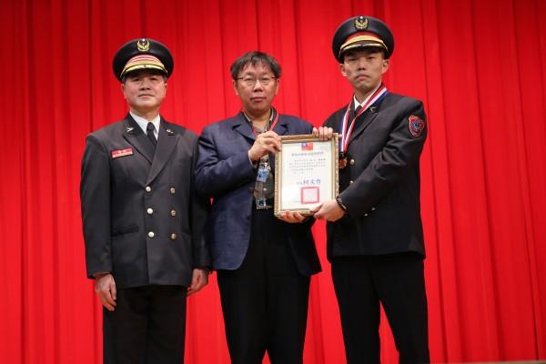 柯文哲(中)頒金龍獎給包括趙浩翎(右)在內的有功消防人員;左為代理局長吳俊鴻。(記者姚岳宏攝)