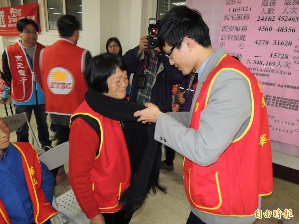 私立建臺中學高二學生黃建澄(右),將自己編織的圍巾,繫在老人頸上,讓她們溫暖在心頭。(記者張勳騰攝)
