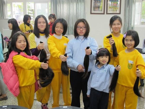 力行國小學童剪下留了多年的長髮,捐給癌童做假髮。(圖由力行國小家長會提供)