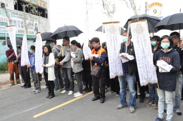 六名殉職消防員的家屬們,下午手持幡旗、捧著靈位前往現場招魂。(記者余瑞仁攝)