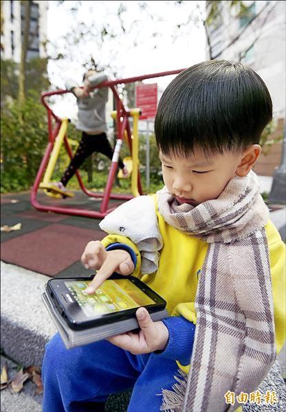 「兒少法」部份條文修正案立法院昨日三讀通過,明定兒童、少年不得超過合理時間持續使用電子產品。圖為小朋友玩手機。(記者方賓照攝)