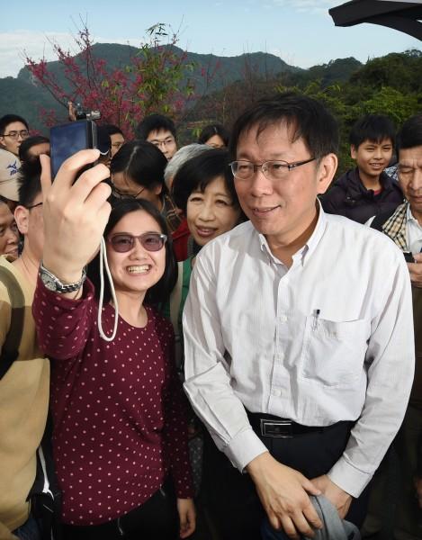 台北市長柯文哲(右)偕同妻子陳佩琪(中)25日參訪台北市立動物園,並搭乘貓纜、走步道,來一場「攬翠之旅」,高人氣引發遊客頻頻爭相合照。(記者廖振輝攝)