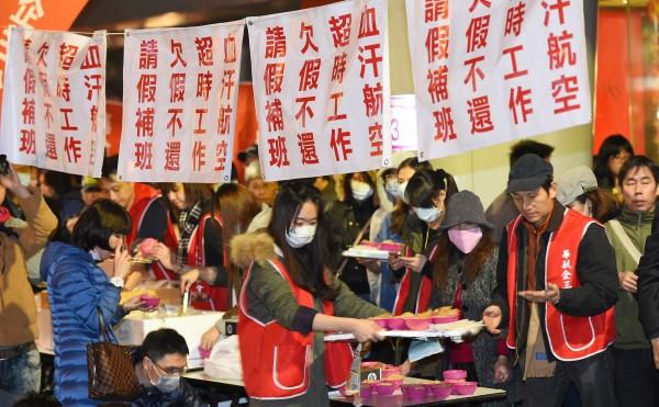 因不滿公司營收上千億,卻只發出每人二萬的年終獎金,華航企三分會22日在台北總公司前發起抗議,寒流來襲時在路邊吃尾牙。(資料照,記者張嘉明攝)