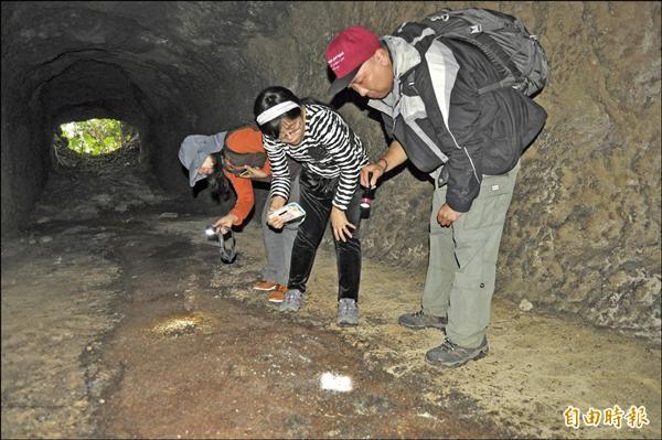 中山大學生物科學系博士後研究員何英毅(右一)等人前往會勘,檢視洞穴滿地的蝙蝠排遺。(記者蘇福男攝)