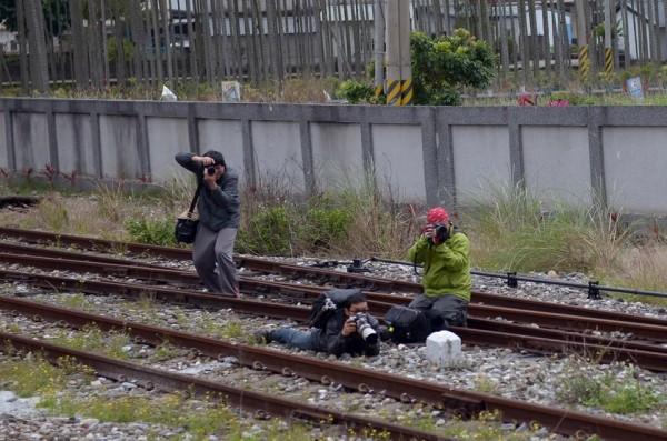 「臥『攝』預備」?!鐵道迷端著單眼相機、大砲趴在花蓮萬榮火車站鐵軌,準備拍進站的CT273蒸汽火車,被批玩命。(取自『台鐵路透社臉書)