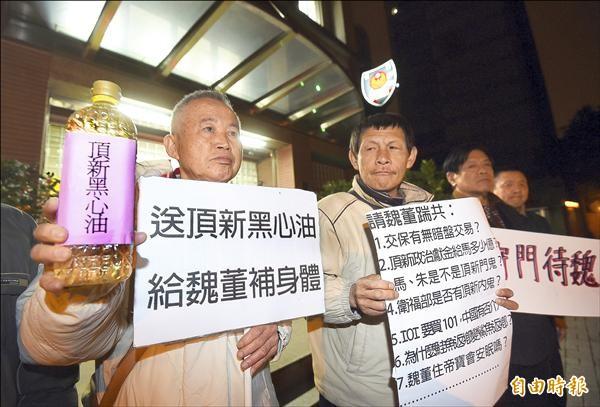 不滿頂新魏應充交保,台灣國王獻極等人帶著黑心油,準備向魏應充抗議。(記者方賓照攝)