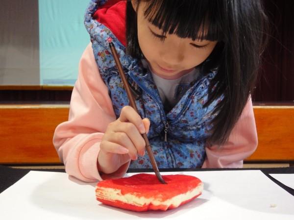 景興國小今年發揮創意,把春聯紙改用吐司替代,墨水則是墨魚汁,小朋友好吃、好玩又健康。(北市教育局提供,記者梁珮綺翻攝)