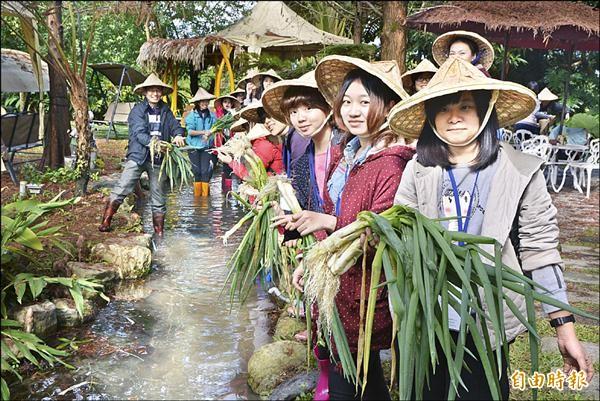 到冬山鄉梅花社區「農STAY」的大學生們體驗農夫生活,到河邊洗蔥。(記者朱則瑋攝)