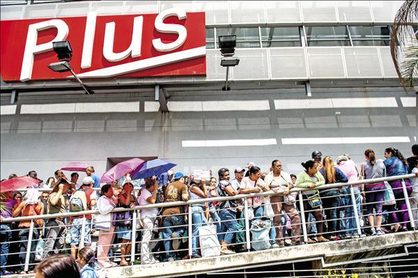 委內瑞拉民眾飽受民生物資短缺之苦,為了採買日用品必須大排長龍。圖為首都卡拉卡斯一家賣場外的排隊人潮。(法新社)