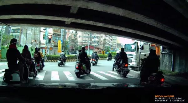砂石車差點撞上大群闖紅燈的機車,然而機車少年們眼看沒發生意外便繼續騎。(擷取自YouTube)