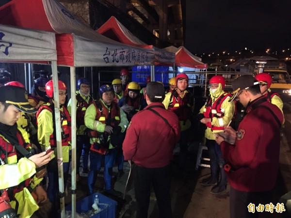 搜救人員經短暫休息後即將搭乘船艇,徹夜搜索河面。(記者曾健銘攝)