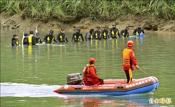 海軍水下作業大隊弟兄排成一條人龍搜尋。(記者劉信德攝)
