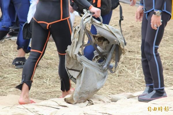 田姓消防員撈到嚴重損壞的行李箱。(記者吳張鴻攝)