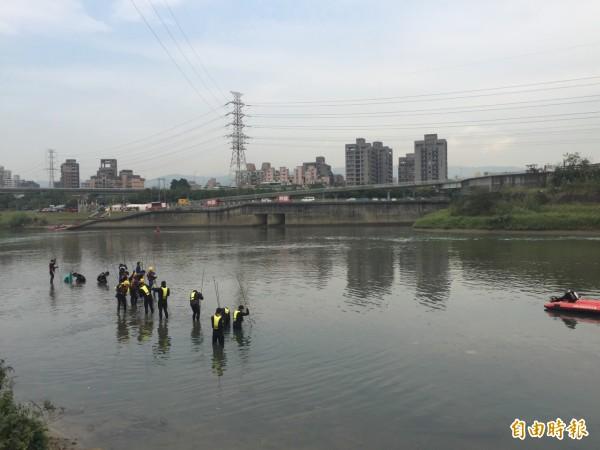 消防員再次用鋼條翻找河床泥土。(記者余衡攝)
