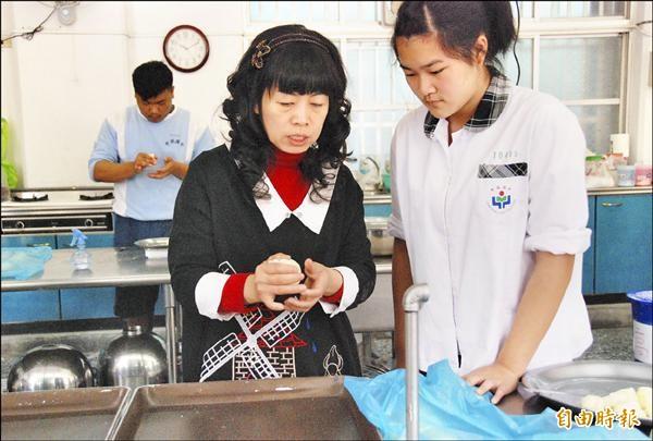 烘焙技藝老師陳淑惠(前左)常舉自己學習障礙的例子鼓勵學生。圖中她正在教學生包有餡料的麵包技巧。(記者陳鳳麗攝)