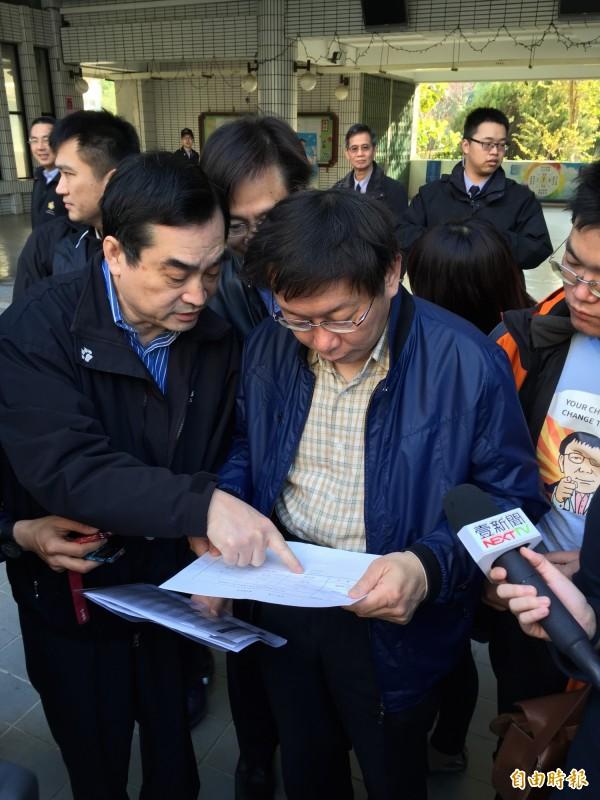 台北市副市長鄧家基(左)向台北市長柯文哲(右)解釋選務情形。(記者梁珮綺攝)