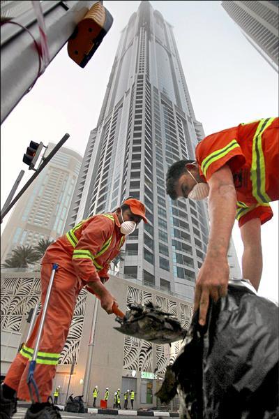 杜拜高七十九層的「火炬塔」(Torch Tower)在當地時間二十一日凌晨驚傳起火,影響樓層達二十層,又因風勢強烈,烈焰殘骸包括玻璃、金屬等四散,火勢撲滅後清潔人員著手清理街道。(歐新社)