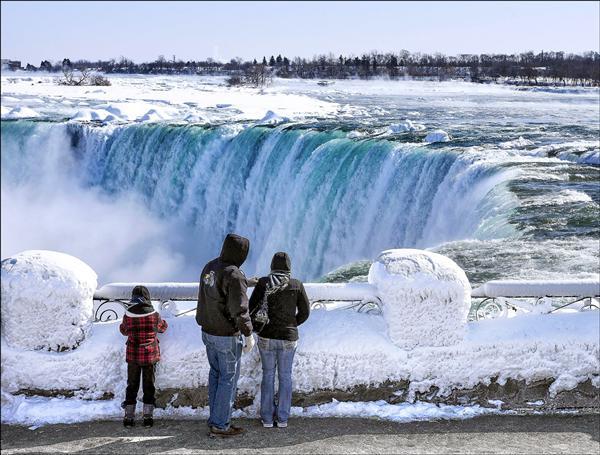 低溫持續重創全美,首都華盛頓二十日更測得破一二○年紀錄的攝氏零下十五度。圖為遊客二十日欣賞近乎冰凍的尼加拉大瀑布。(法新社)
