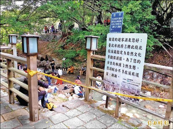 年節期間,許多民眾不顧警告標語與法令,捲起褲管踩在北投石保護區的河段。(記者郭逸攝)