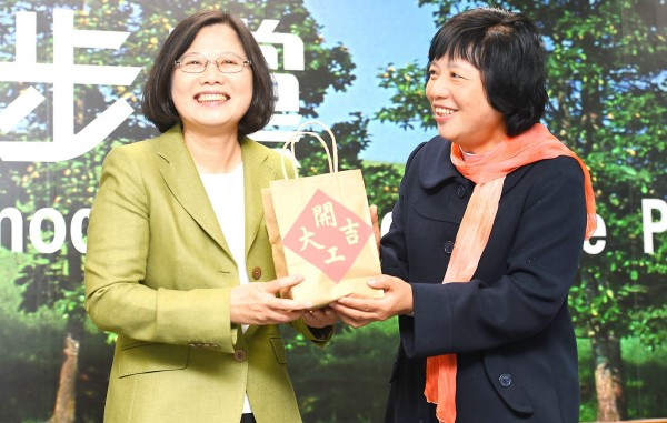 Peng Hsiu-chun, right, widow of Chang Sen-wen, who owned the Chang Pharmacy that was demolished in the Dapu Incident in Miaoli County, presents Democratic Progressive Party (DPP) Chairperson Tsai Ing-wen with homemade ginger sugar at the DPP's Taipei headquarters yesterday, the first working day of the new lunar year. Photo: Chang Chia-ming, Taipei Times