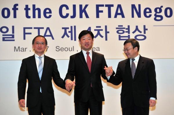 中韓FTA今天進行草簽,根據出爐的條文研究,對台灣的衝擊並不像馬政府選前所宣稱的那麼嚴重,圖為中日韓在去年3月商談FTA時的畫面。(資料照,法新社)
