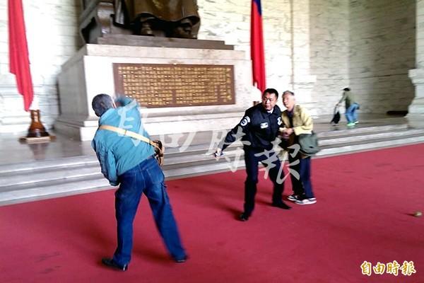 台灣國成員在228前夕,至中正紀念堂向蔣中正銅像潑漆。(記者蘇芳禾攝)