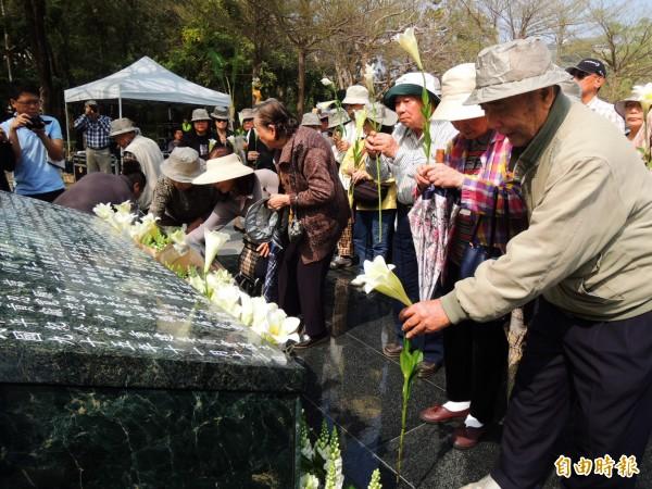 228受難者家屬在紀念碑前獻花。(記者葛祐豪攝)