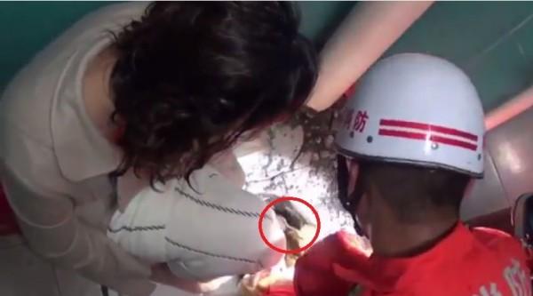 消防員用湯匙(紅圈處)將女子的腿救出。(圖片擷取自Youtube)