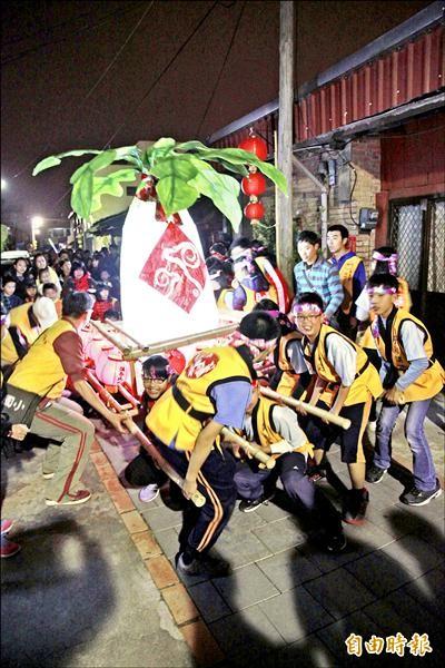 小朋友齊力抬起自製的大型好彩頭燈,讓社區民眾跟隨,繞行遊街。(記者鄭鴻達攝)