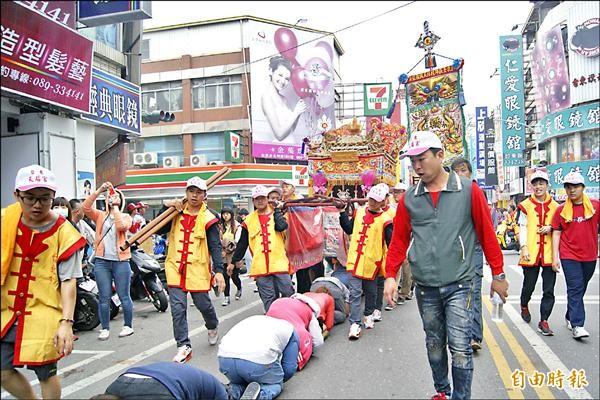 元宵昨天下午起展開一連兩天的遶境祈福活動,七十家廟宇近百個陣頭在街頭繞行,民眾在中華路上排長龍下跪,讓天后宮神轎從頭上而過,驅邪祈平安。在越南即信奉媽祖的新移民(右圖)也穿上傳統服飾,走在遶境隊伍裡。(記者王秀亭攝)