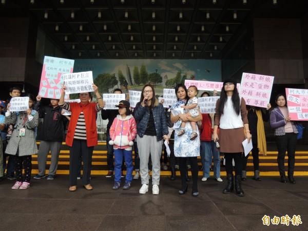 一群來自中國、越南、印尼等地的新移民,今早在台北市政府門口舉標語抗議柯文哲的「進口說」。(記者葉冠妤攝)