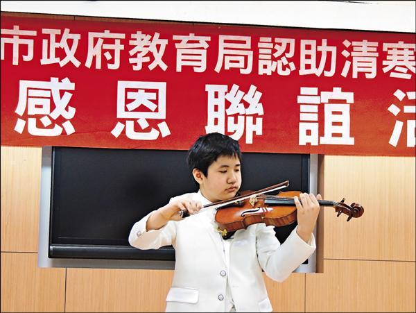 去年在日本獲得國際鋼琴賽少年組總冠軍的小五生江璟亮,昨天現場彈鋼琴及拉小提琴,感謝認助人。(台北市教育局提供)