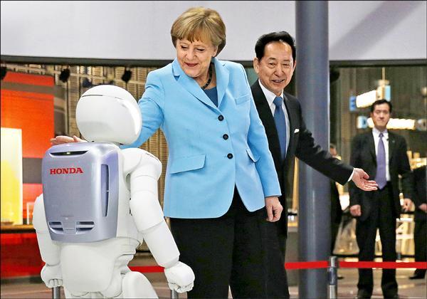 梅克爾九日參觀東京都日本科學未來館,與本田機器人ASIMO握手。(路透)