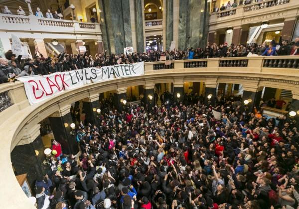 抗議學生在州議會內進行抗議,幾乎癱瘓整個州議會大廈,用這種方式來抗議,美國執法單位一直以來存在的種族歧視問題。(美聯社)