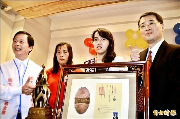 就讀大葉大學休閒管理研究所的黃靖茹(右二),獲得「周大觀文教基金會─全球熱愛生命獎章」。(記者顏宏駿攝)
