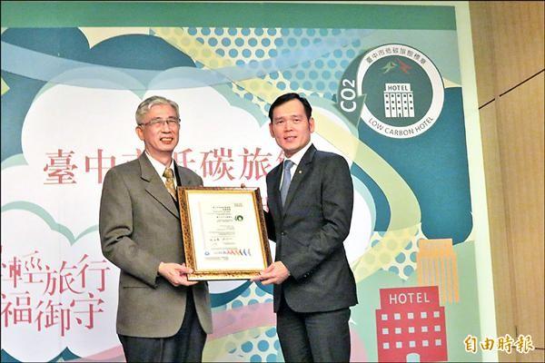 觀光旅遊局長陳盛山(左)頒發台中市低碳旅館認證證書給17家業者。(記者蘇金鳳攝)