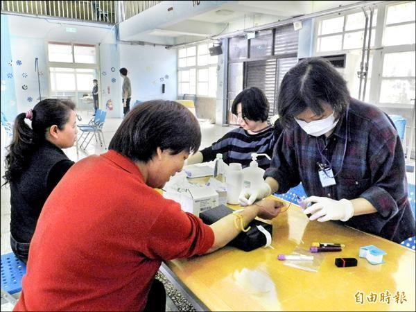 流行病學研究計畫團隊在台西和崙豐國小為鄉民抽血驗尿。(記者鄭旭凱攝)
